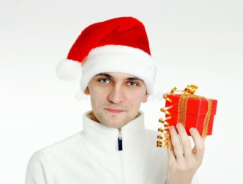 Mens in een Kerstmanhoed met Kerstmisgift royalty-vrije stock afbeelding