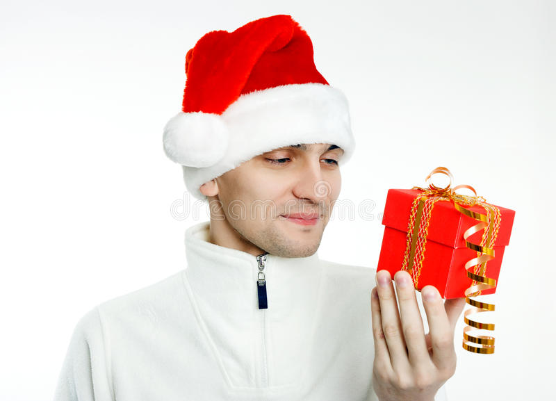 Mens in een Kerstmanhoed met Kerstmisgift stock afbeelding