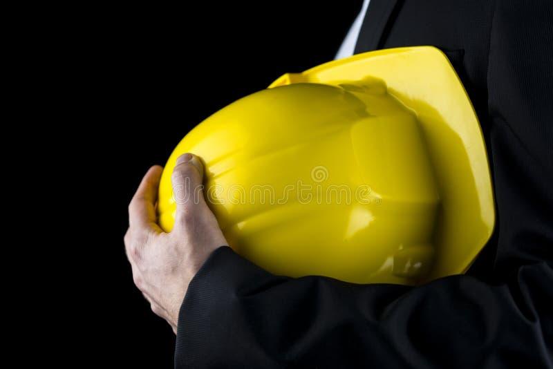 Mens in een kostuum die een gele bouwvakker houden stock foto's