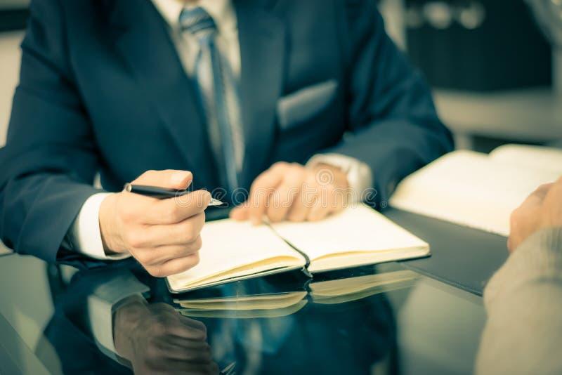 Mens in een kostuum die een pen houden en nota's nemen stock foto's