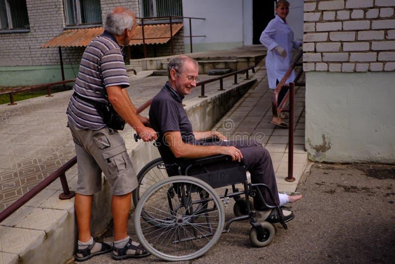 mens in een rolstoel bij de noodsituatieruimte van het stadsziekenhuis stock fotografie