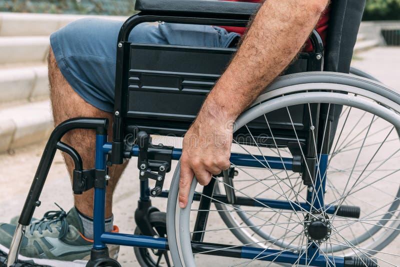 Mens in een rolstoel met zijn hand op het wiel royalty-vrije stock afbeeldingen