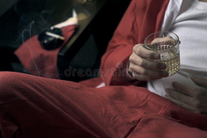 Mens in een santakostuum het drinken wisky stock fotografie
