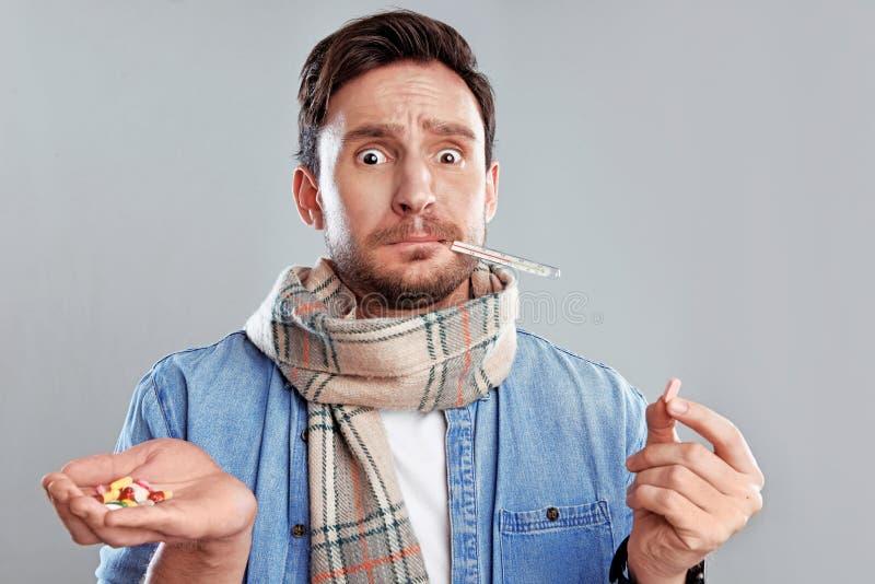 Mens in een thermometer van de sjaalholding en een handhoogtepunt van pillen op een witte achtergrond wordt geïsoleerd die royalty-vrije stock foto's