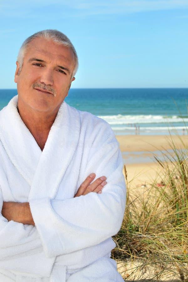 Mens in een toweling robe door het overzees royalty-vrije stock fotografie
