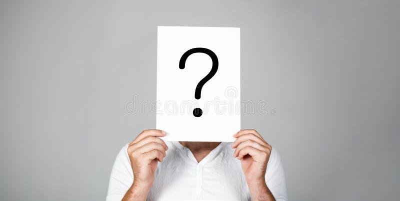 Mens een vraag Het twijfelachtige Vraagteken van de mensenholding Problemen en oplossingen Vraagteken, symbool Peinzend Mannetje  royalty-vrije stock foto