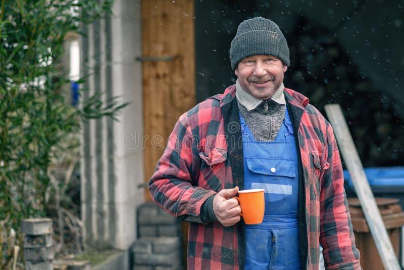 Mens in een warme jasje en beanie het drinken koffie stock afbeeldingen