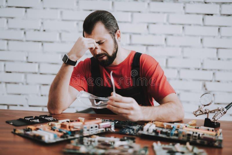Mens in Eenvormig met Gebroken Motherboards in Winkel stock foto