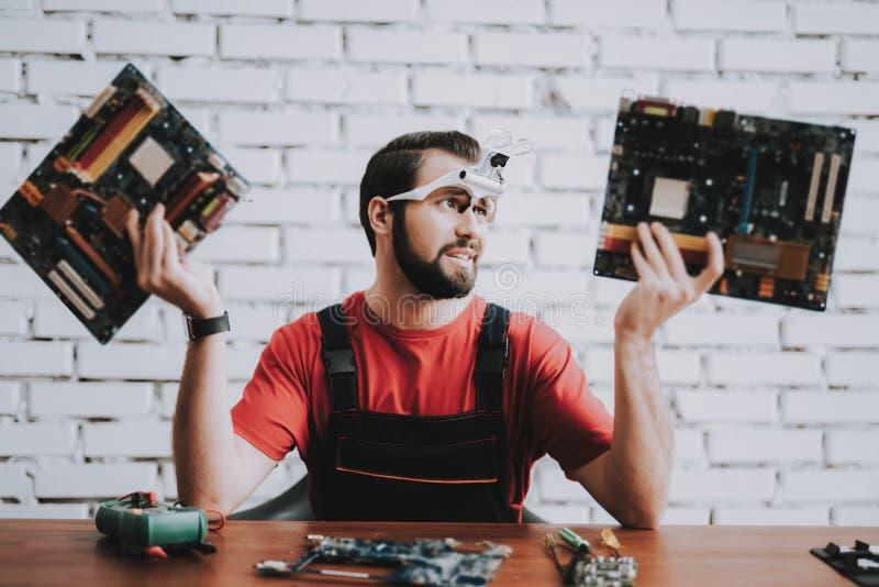 Mens in Eenvormig met Gebroken Motherboards in Winkel royalty-vrije stock afbeeldingen