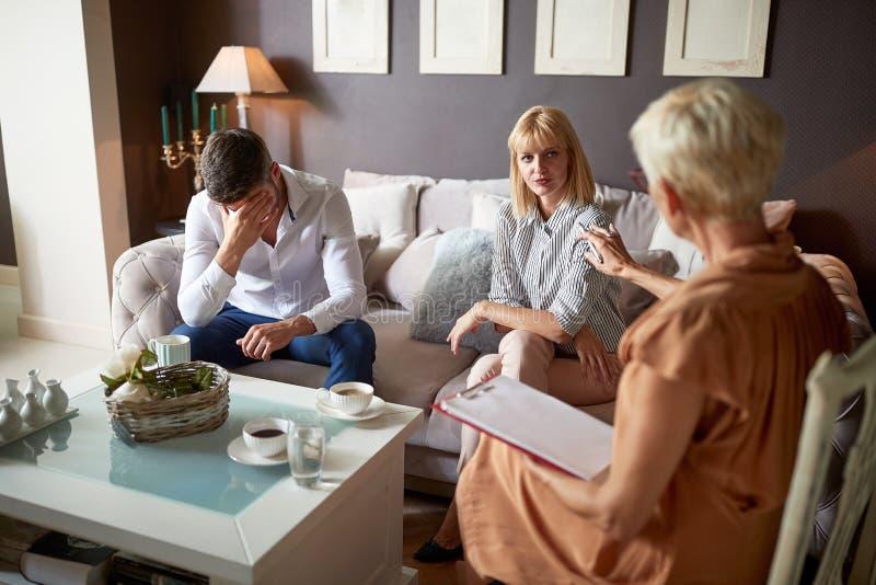Mens in emotioneel probleem met vrouw bij psycholoog stock fotografie