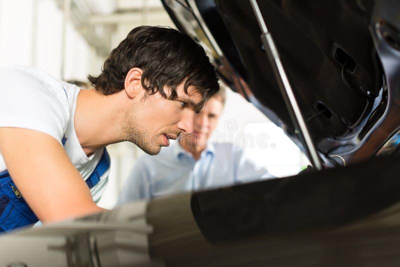 Mens en autowerktuigkundige die onder een kap kijken stock fotografie