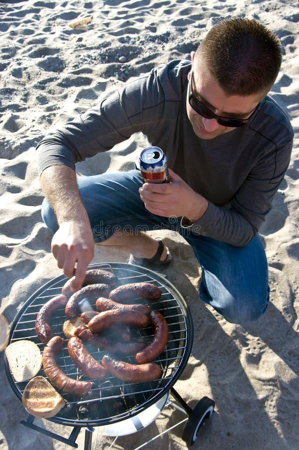Mens en barbecue op strand royalty-vrije stock afbeelding