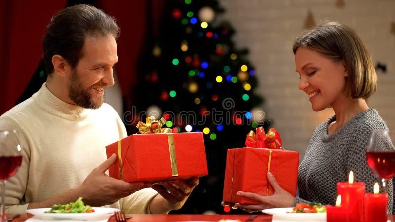 Mens en de dame die Kerstmis de ruilen stellen, comfortabele romantische avond voor paar voor royalty-vrije stock fotografie