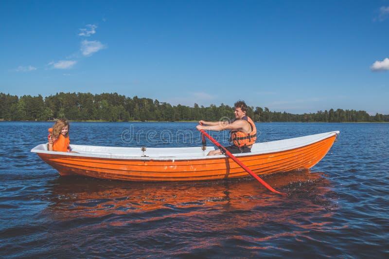 Mens en het kind, het meisje in de boot, die op het meer roeien royalty-vrije stock fotografie