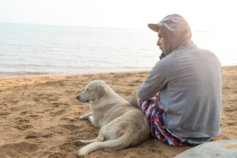 Mens en hondzitting samen op zandstrand op vakantietijd royalty-vrije stock foto