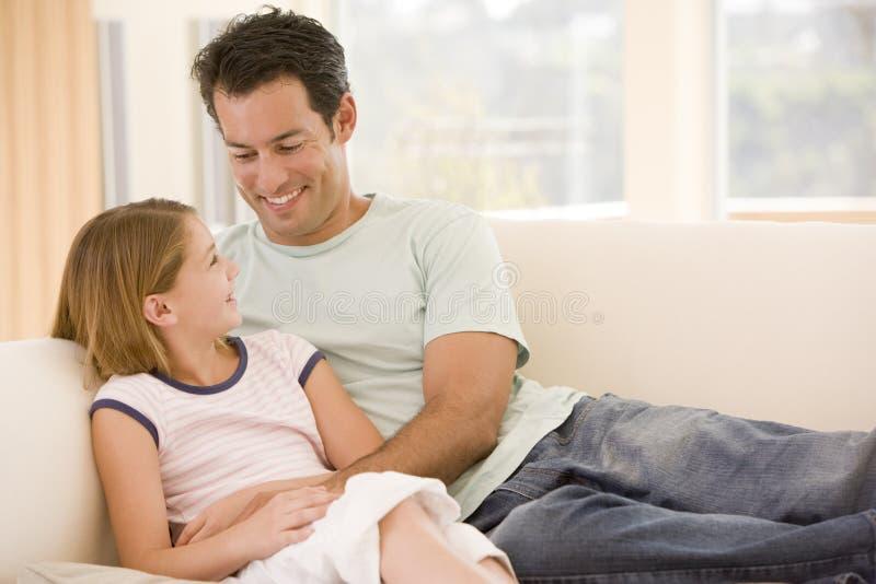 Mens en jong meisje in woonkamer het glimlachen stock afbeeldingen