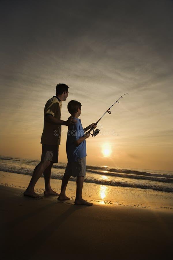 Mens en jonge jongen die in branding vissen royalty-vrije stock foto's