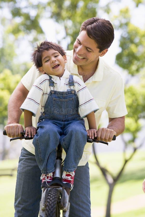 Mens en jonge jongen op een fiets die in openlucht glimlacht stock afbeelding