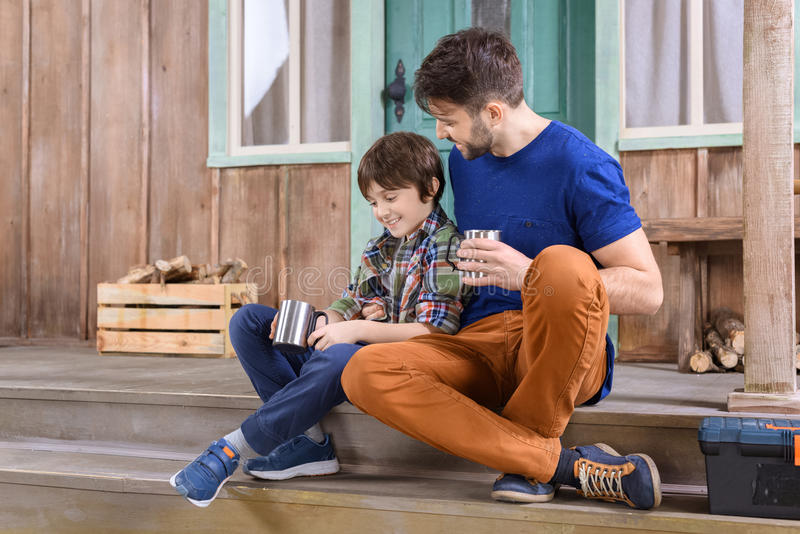 Mens en jongen die met metaalkop theeën op portiek zitten stock afbeeldingen