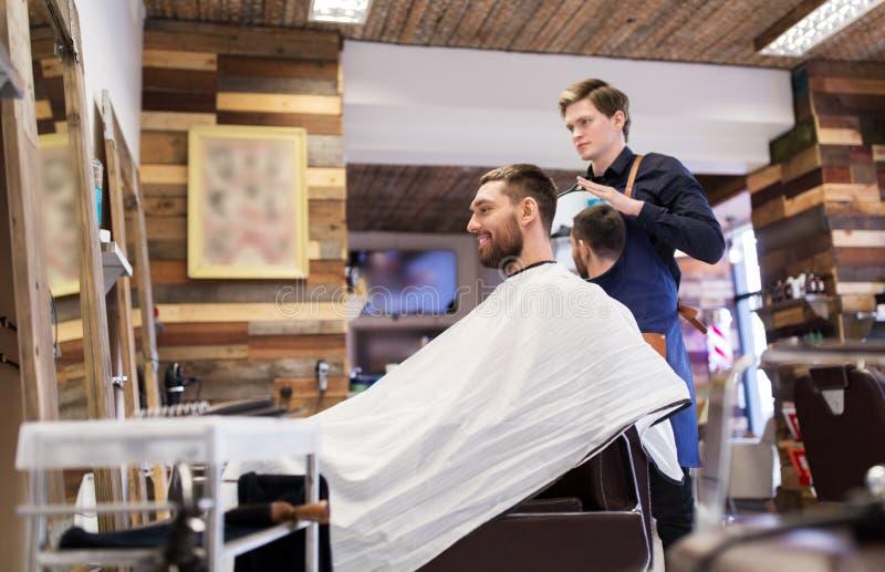 Mens en kapper met spiegel bij herenkapper royalty-vrije stock foto's