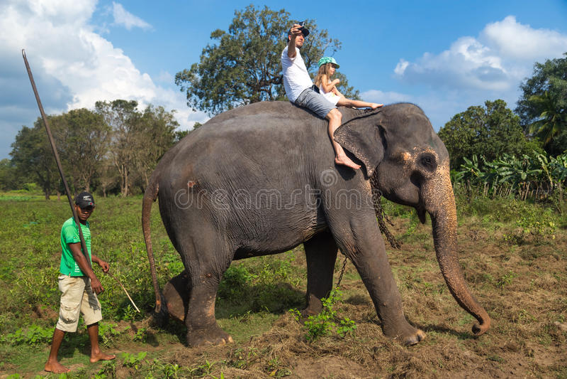 Mens en kind die op de rug van olifant berijden royalty-vrije stock foto