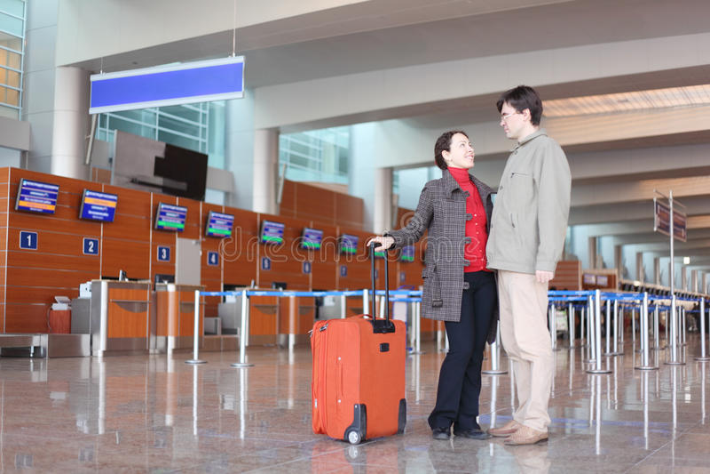 Mens en meisje met koffer die zich in luchthaven bevindt stock afbeelding