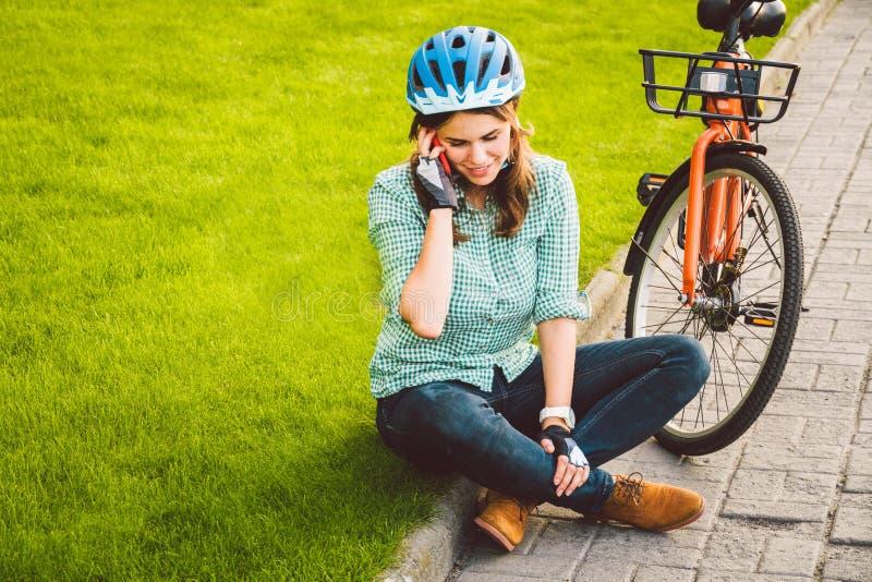 Mens en stads rollende fiets, milieuvriendelijk vervoer De mooie jonge Kaukasische zitting die van de vrouwenarbeider op gr. rust royalty-vrije stock afbeelding
