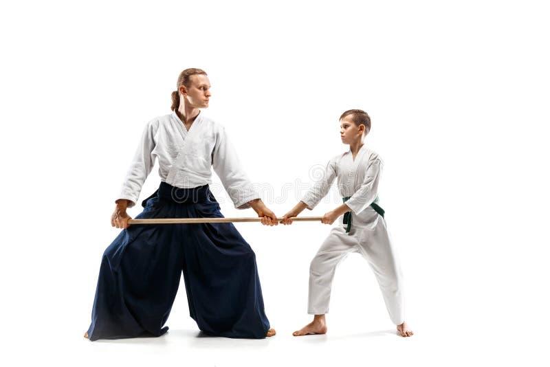 Mens en tienerjongen het vechten met houten zwaarden bij Aikido-opleiding in vechtsportenschool royalty-vrije stock fotografie
