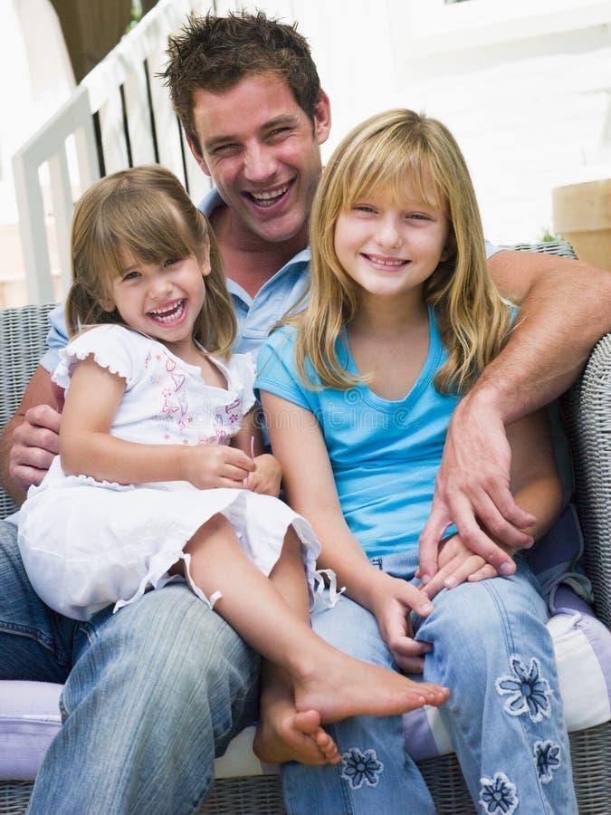 Mens en twee jonge meisjes die bij terras het glimlachen zitten stock afbeelding