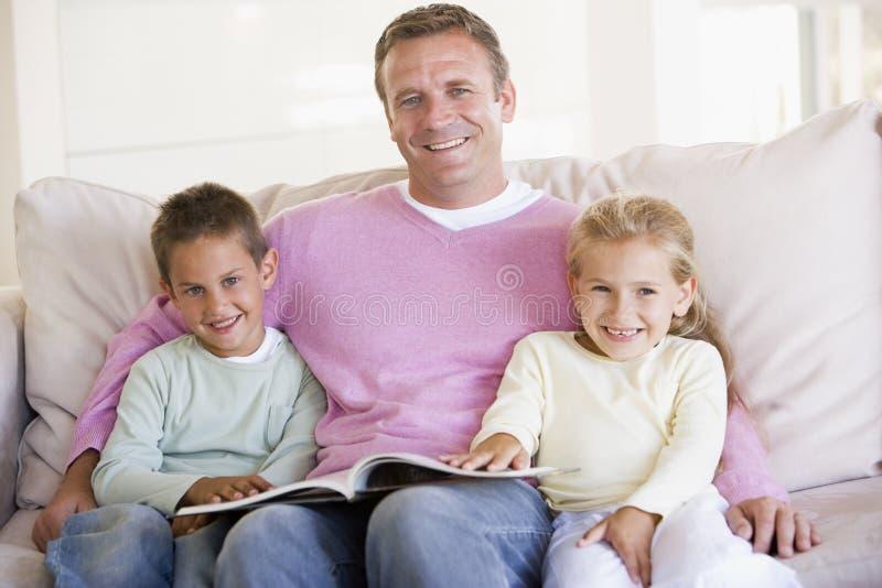 Mens en twee kinderen die in woonkamer zitten stock afbeeldingen