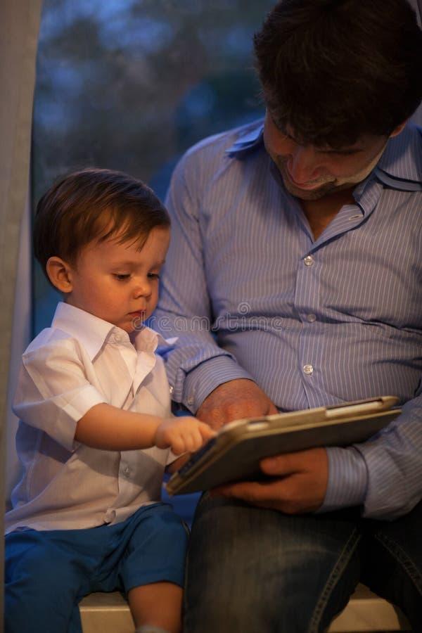 Mens en weinig jongen die met tablet spelen royalty-vrije stock afbeeldingen