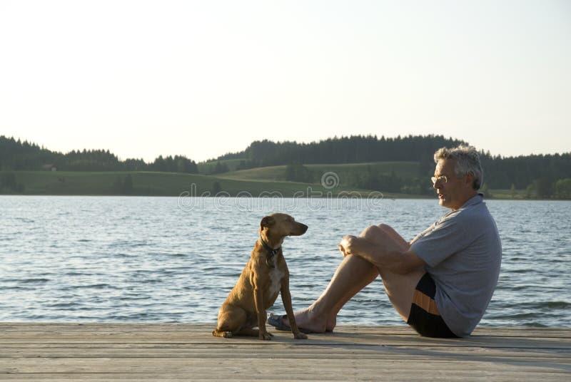 Mens en zijn hond stock afbeelding