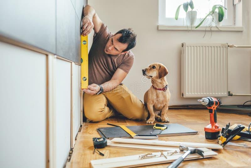 Mens en zijn hond die het vernieuwingswerk thuis doen royalty-vrije stock afbeelding