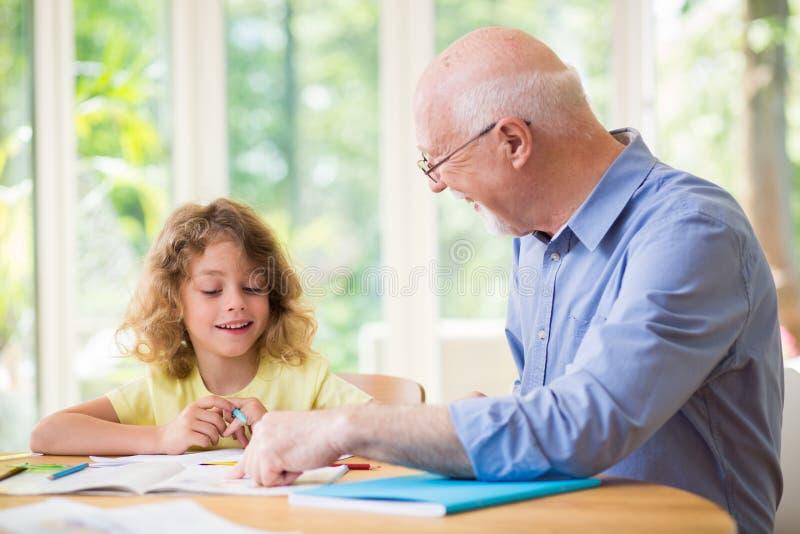 Mens en zijn kleinkind die thuiswerk na school doen stock afbeeldingen