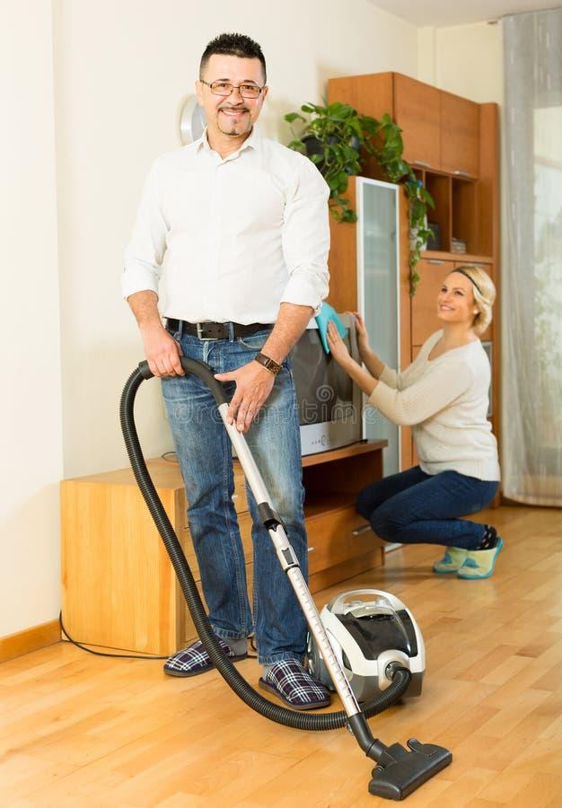 Mens en zijn vrouw die thuis schoonmaken stock foto's