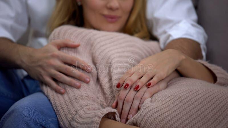 Mens en zwangere vrouw die, mannelijke hand die op vrouwelijke buik, geluk liggen koesteren royalty-vrije stock foto