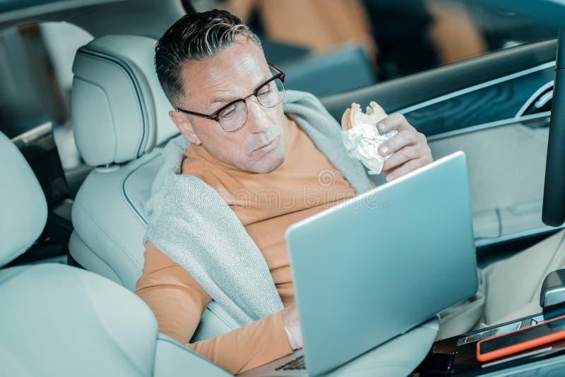 Mens eten die op zijn vrouw in de auto wachten stock afbeeldingen
