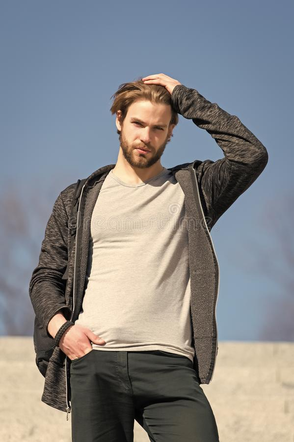 Free Mens Fashion And Style. Man With Beard In Casual Wear Touch Hair On Sunny Outdoor, Fashion. Macho Stand On Blue Sky Royalty Free Stock Image - 134014676