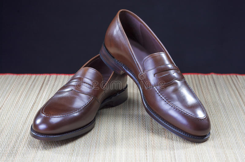 Mens Footwear Concepts. Pair of Stylish Brown Penny Loafer Shoes Placed on Straw Surface against Black. royalty free stock photography