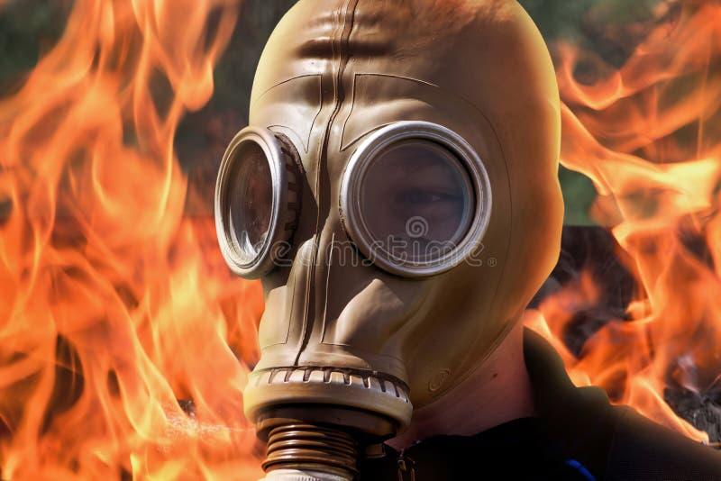 Mens in gasmasker op achtergrond van brand tijdens brand Bedwingende spar stock afbeelding