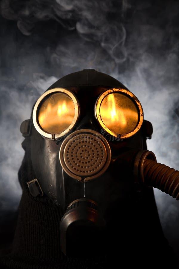 Mens in gasmasker over rokerige achtergrond stock foto