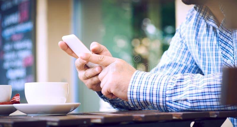 Mens gebruikend een celtelefoon op koffieterras en drinkend koffie De mens drinkt koffie Mens die cellphone gebruikt Bemant hande stock fotografie