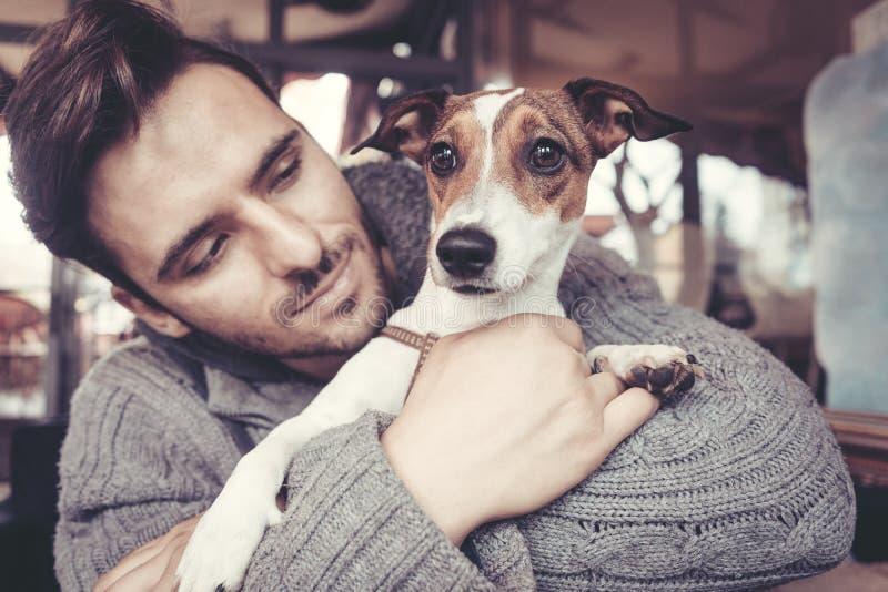 Mens geknuffel met zijn hond in de winter stock afbeelding