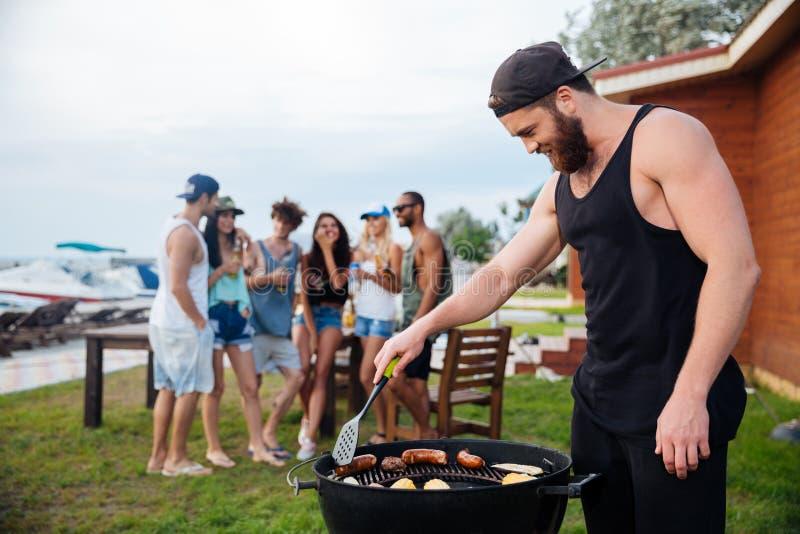 Mens geroosterd koken sauseges en groenten op barbecuepartij stock afbeelding
