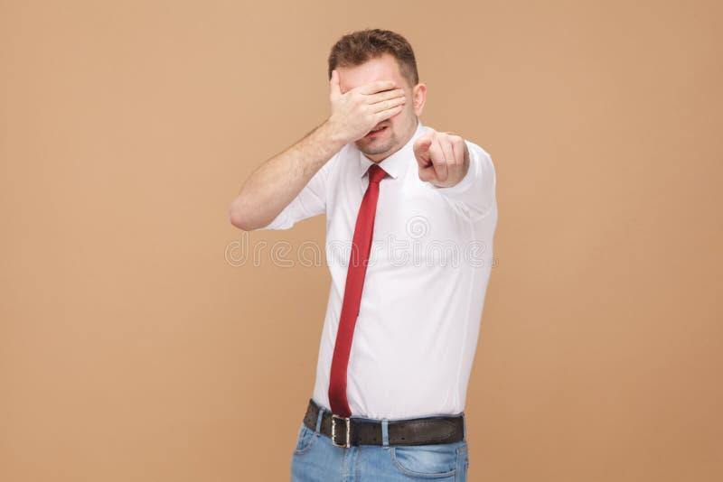 Mens gesloten ogen en het richten van vinger op camera stock afbeeldingen