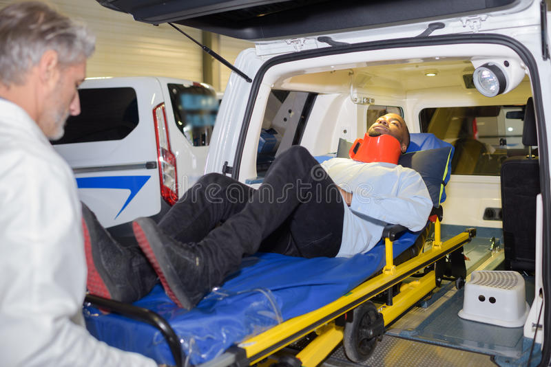 Mens in halssteun die in ziekenwagen worden geladen royalty-vrije stock afbeelding