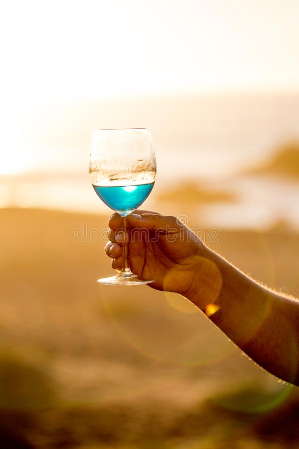 Mens hand holding glass of spanish blue with wine on sea ocean background royalty free stock image