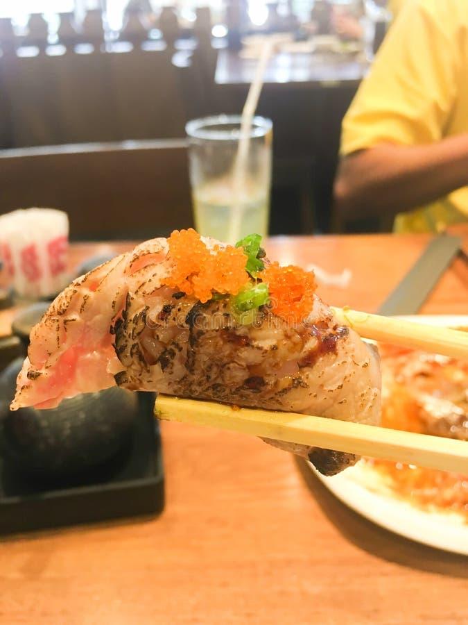 Hand holding wooden sticks sushi at Japanese restaurant royalty free stock photo
