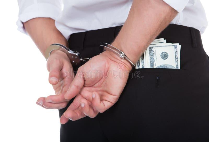 Mens in handcuffs met bankbiljetten in zijn zak royalty-vrije stock foto