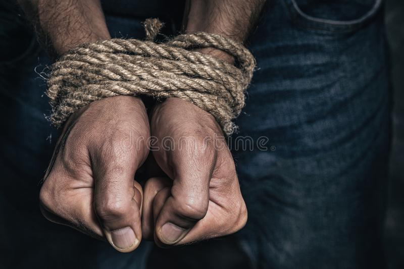 Mens hands tied with a rope. Concept of imprisonment in modern society royalty free stock image